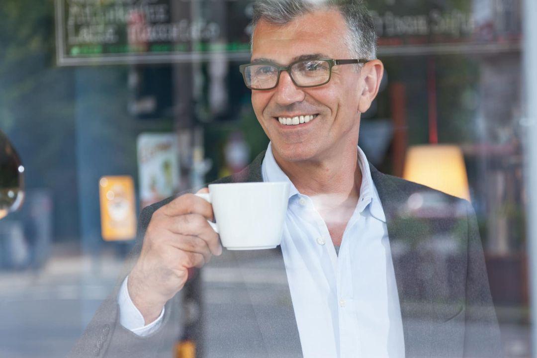 Glücklicher Geschäftsmann mit Kaffeetasse in der Hand