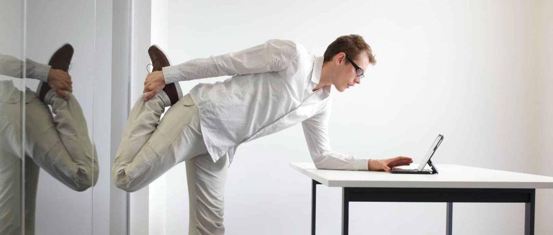 Junger Mitarbeiter macht Dehnübungen am Arbeitsplatz