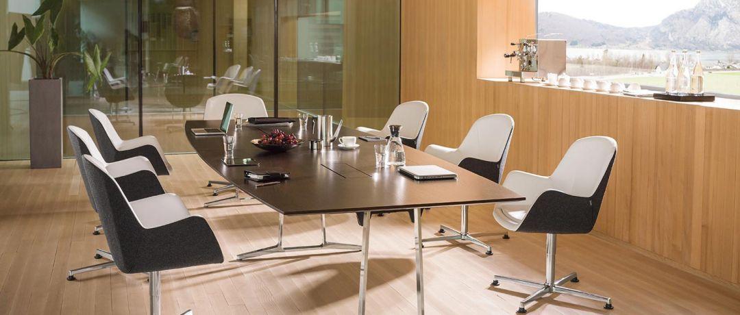 Brauner bootsförmiger Tisch mit 7 Konferenzstühlen in schwarz weiß