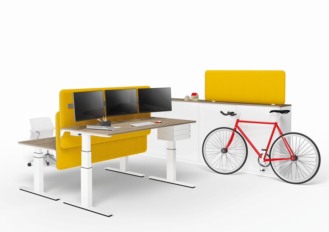 Sitz-Steh-Schreibtische mit gelber Akustikwand und einem Schrank