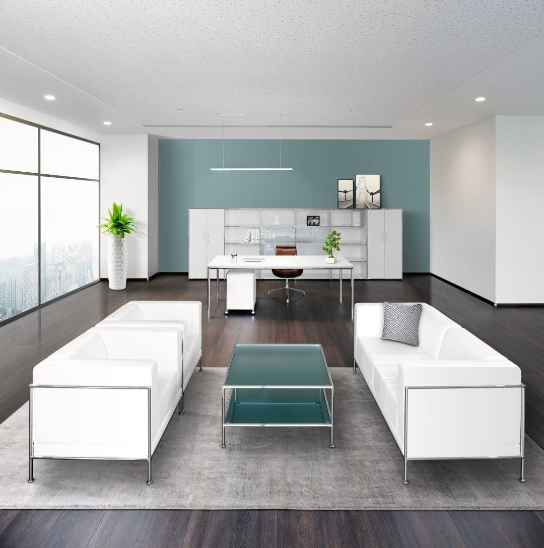 Moderne Sofas in weiß mit  Chrom-Beinen in verschieden Ausführungen mit passendem Glastisch. Im Hintergrund der Arbeitsbereich gehalten