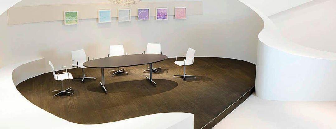 Ovaler Besprechungstisch mit weißen Stühlen
